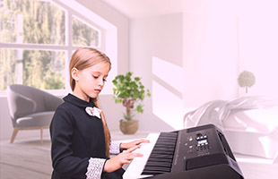 side view of young girl playing Yamaha PSR-EW310 in living room