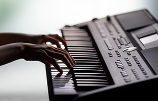side view of hands playing Yamaha PSR-SX600