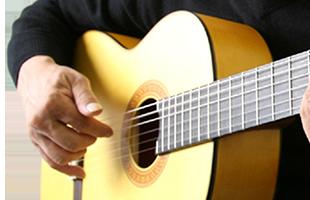 close-up image of hand strumming Yamaha classical guitar