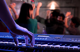 close-up image of hand playing a chord on Yamaha PSR-SX600 with party scene in background