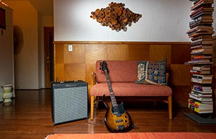 Ampeg Rocket Bass 112 in living room alongside couch with bass guitar resting against it