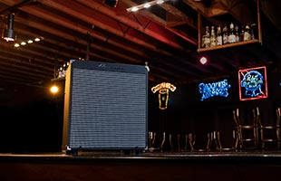 Ampeg Rocket Bass 112 resting on bar in barroom with neon beer signs in the background