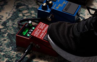 close-up image of foot stepping on Boss RC-5 Loop Station on carpet alongside other pedals