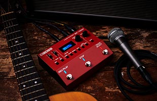top view of Boss RC-500 Loop Station sitting on wood floor surrounded by guitar neck, amplifier grille and microphone