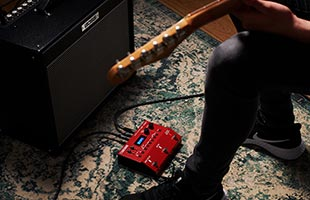 close-up view of guitar player's feet, guitar headstock and practice amplifier arrayed around Boss RC-500 Loop Station on carpet