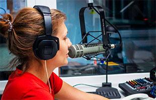 broadcaster in broadcast studio speaking into Electro-Voice RE20