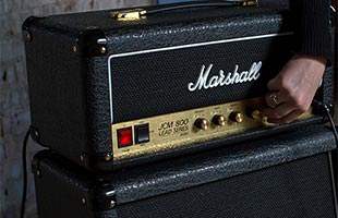 close-up image of Marshall SC20H sitting on top of speaker cabinet with hand adjusting controls