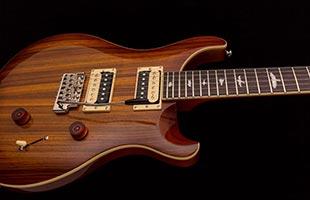 close-up image of PRS SE Custom 24 body showing zebrawood exotic veneer and Vintage Sunburst finish