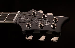 detail image of PRS SE Mark Holcomb showing top of headstock and black chrome hardware