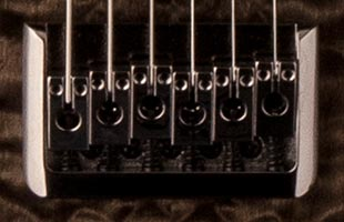 detail image of PRS SE Mark Holcomb showing plate-style strings-through-body bridge