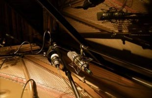 close-up image of microphones positioned to record from inside grand piano cabinet