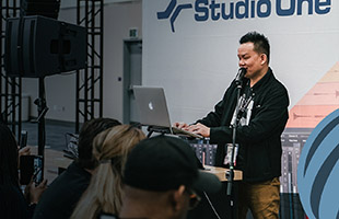PreSonus seminar with crowd watching presenter on stage with microphone and laptop computer