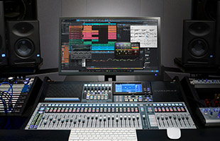 front perspective view of recording studio desk with mixing controller, computer monitor and studio monitor speakers