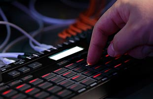 close-up image of Korg SQ-64 with musician's hand pressing step button
