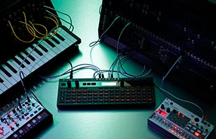 Korg SQ-64 on table surrounded by and connected to other synthesizers