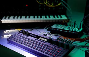 Korg SQ-64 on table with other synthesizers in background