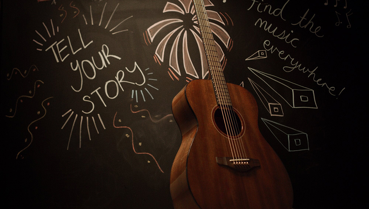 Lifestyle image of STORIA guitar with chalkboard writing: Find the music everywhere! Tell your story