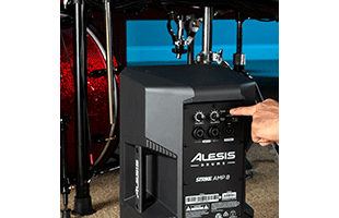 close-up image of Alesis Strike Amp 8 in front of drum kit with hand adjusting Contour EQ control on rear panel