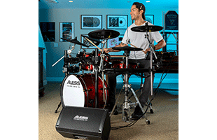 wide angle image of drummer in practice space with Alesis Strike Amp 8 in front of drum kit