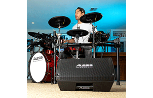 image of drummer playing drums in practice space with Alesis Strike Amp 8 close-up in foreground