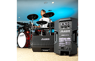 image of drummer playing drums in practice space with two Alesis Strike Amp 8 units in foreground, one positioned horizontally angled upward showing the front and underside and the other positioned vertically showing the rear panel
