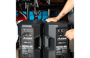 close-up image of two Alesis Strike Amp 8 rear panels in front of drum kit with hand plugging in XLR cable to connect them