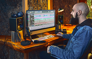 musician sitting in front of table with desktop computer and components of Mackie Studio Bundle set up for recording