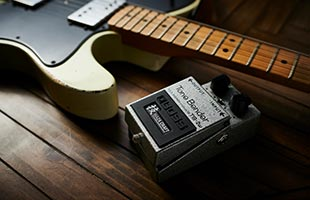 Boss TB-2W Tone Bender sitting next to electric guitar on wooden floor
