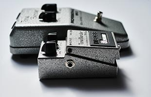 perspective view of Boss TB-2W Tone Bender alongside Sola Sound Tone Bender MK II showing tops and left sides