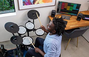 drummer playing Roland TD-07KV in living room with desktop computer on table in background running music recording software
