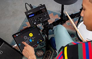 over-the-shoulder close-up view of drummer interacting with Melodics drum lesson software on tablet computer while seated at Roland TD-07KV