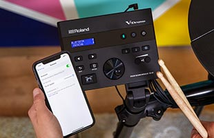 point-of-view image of drummer holding smartphone and drumsticks while sitting at Roland TD-07KV