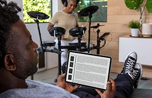 drummer playing Roland TD-07KV in living room using headphones with friend reading tablet computer in foreground