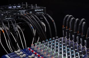 rear view of Roland TD-50X connected with audio cables connecting it to mixer in foreground