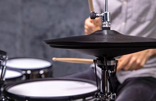 close-up image of drummer playing Roland electronic drum set with Roland VH-14D in foreground