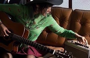 guitarist practicing on sofa with Yamaha THR30IIA Wireless