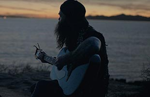 Tim Armstrong sitting on beach playing Fender Tim Armstrong Anniversary Hellcat
