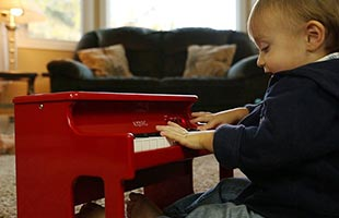 toddler playing Korg TinyPiano in living room