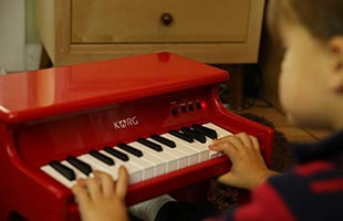 close-up over-the-shoulder view of toddler playing Korg TinyPiano on floor with desk drawer in background
