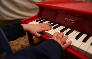 close-up image of toddler's hands playing Korg TinyPiano