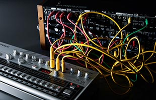 Roland TR-06 on tabletop connected via patch cables to eurorack modular synthesizer in background