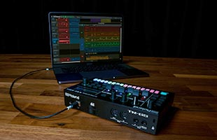 rear view of Roland TR-6S sitting table connected via USB to laptop computer in background