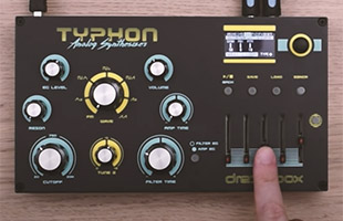 Dreadbox Typhon synthesizer on wooden table with screen showing modulation assignment interface and user's hand manipulating slider