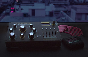 Dreadbox Typhon synthesizer on table in front of window with shutter shades and wristband