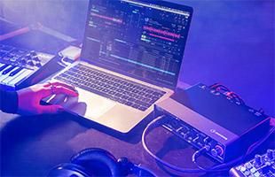 laptop running DJ software next to Steinberg UR24C