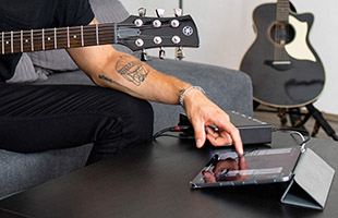 cropped side view of guitarist recording performance using iPad and Steinberg UR24C