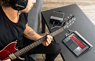 guitarist wearing headphones recording performance using iPad and Steinberg UR24C
