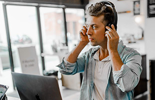 internet streaming personality in office wearing headphones in front of laptop computer
