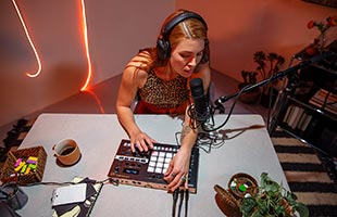 musician sitting at table wearing headphones and singing into microphone connected to Roland Verselab MV-1