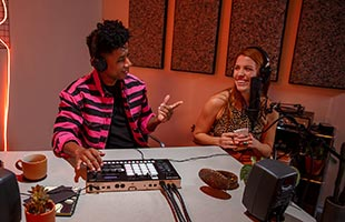 two musicians sitting at desk wearing headphones and recording with Roland Verselab MV-1